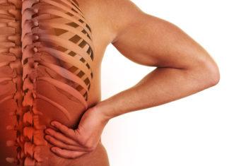 Hand hält sich den schmerzenden Rücken mit 3D-Ansicht der Wirbelsäule